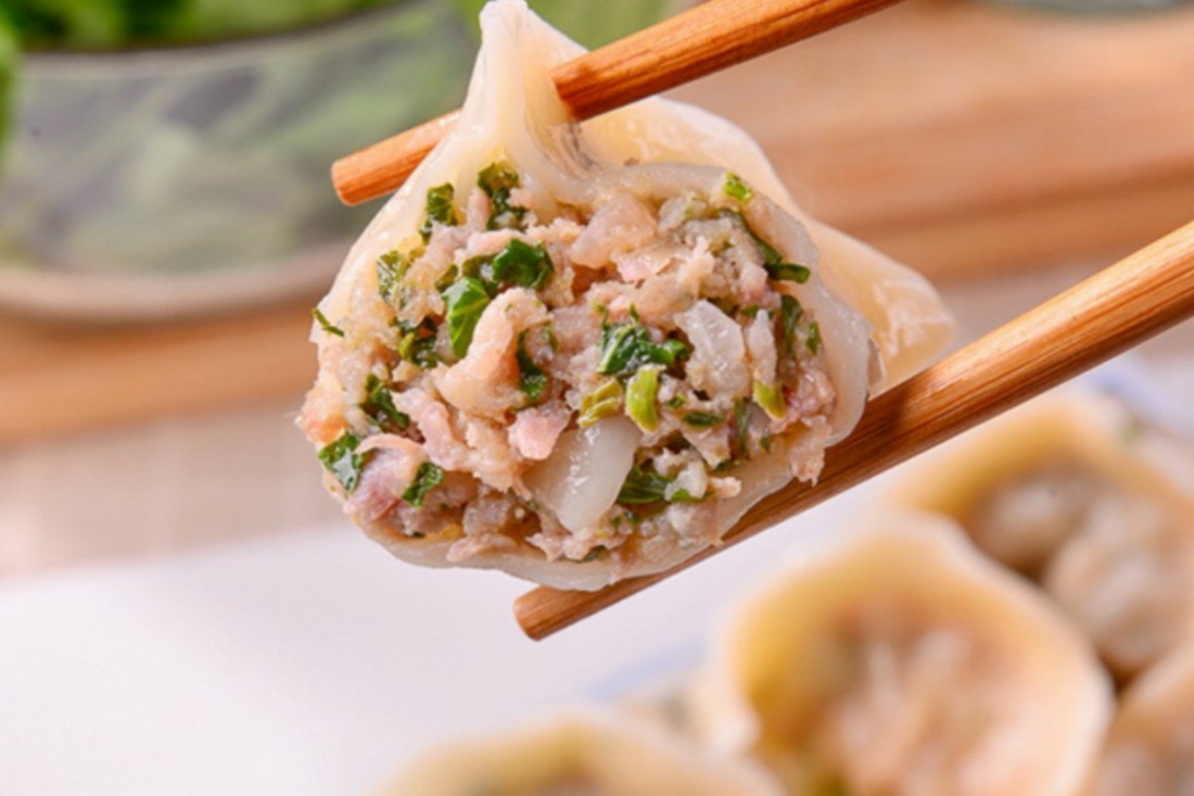 Photo of Joanne's dumplings held in chopsticks with vegetable and meat ingredients looking tasty